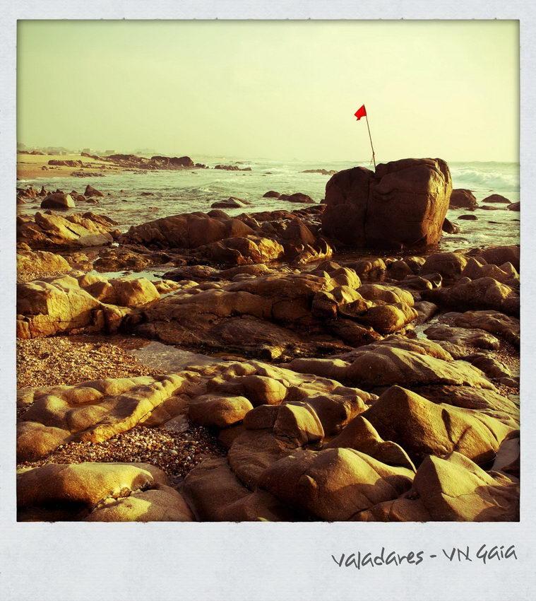 Praia rochosa com uma bandeira vermelha nas rochas