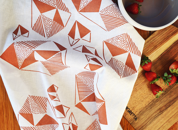Image of the Pattern Play Copper Tea Towel with cutting block