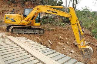 Na entrada para a Granja Mafra, com o auxílio de uma escavadeira, profissionais da Prefeitura trocam uma ponte de lugar