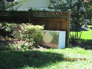 Refrigerator hidden between fence and shrubbery