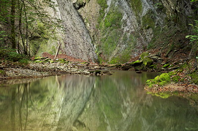 Image of a sandstone cliff reflected on the water of Fornant river