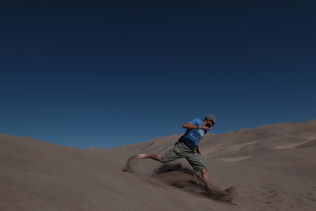 Running with long strides down a sand dune at Great Sand Dunes National Park.