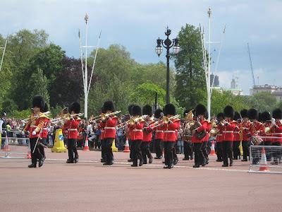 En el Cambio de Guardia los guardias coronados por enormes sombreros de pelo realizan un desfile al ritmo de diferentes temas musicales, tanto militares, como de otros estilos más actuales.
