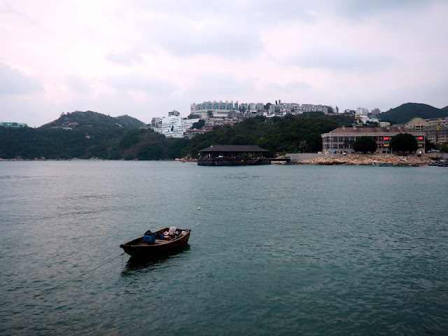 Stanley waterfront and harbour, with a small fishing boat and Blake Pier in the background, Hong Kong
