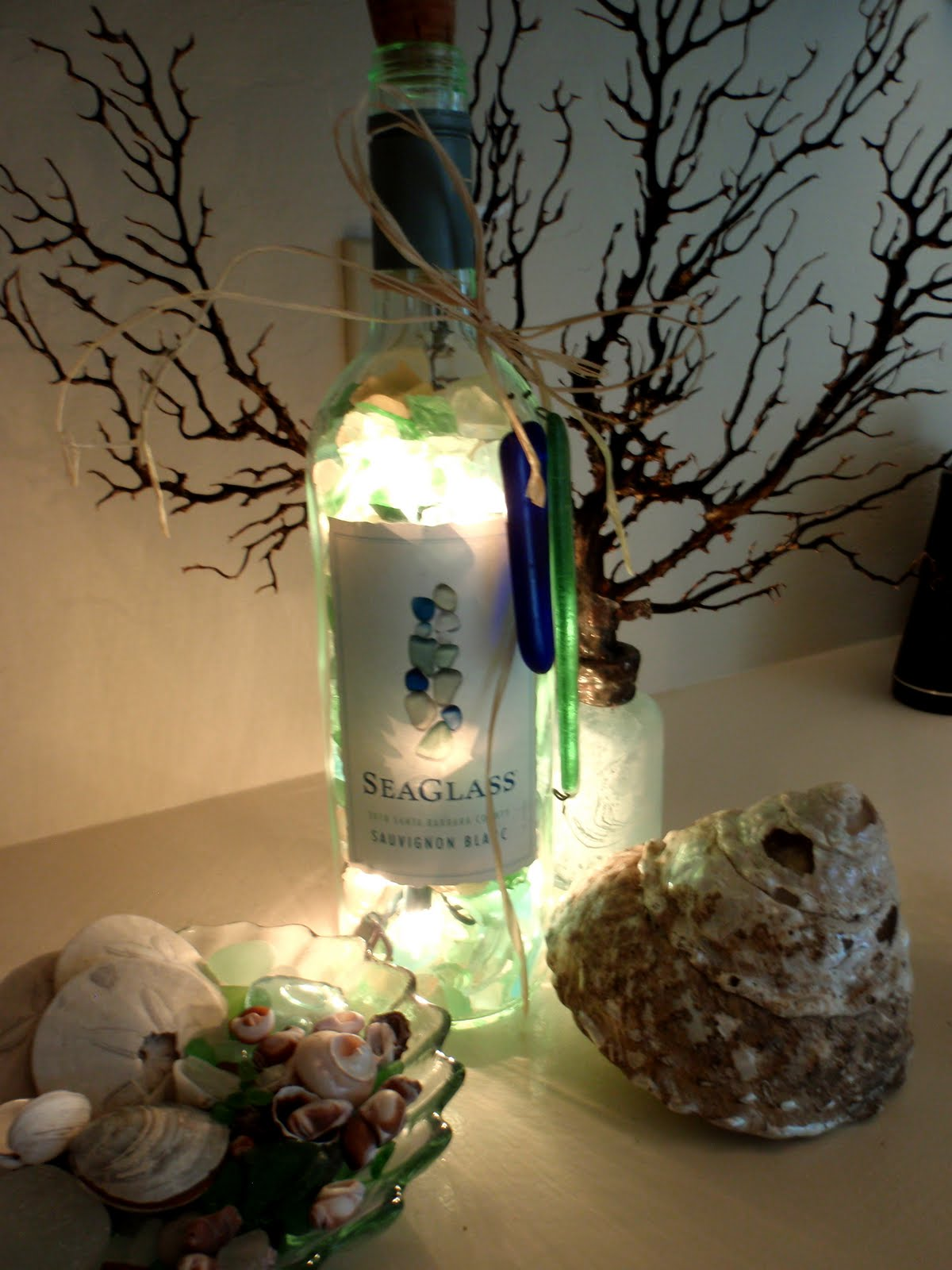 An Empty Pretty Wine Bottle, A String Of Lights And A Collection Of Pretty Sea  Glass