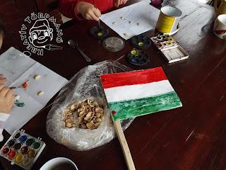 Szöveg: Asztali csatatér zászlóval, vízfestékkel, pisztácia-héjakkal, lurkókkal. Kép: A fenti kép kinagyítva: zacskóban héjak, zászló rajta, két belogó kezecske, amint ecsettel pisztécia-héjakat festenek vízfestékkel. Kerek és négyszögletú vízfesték is van asz asztalon.