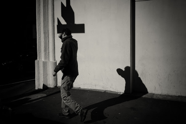 A man shields his eyes against the sun and casts a shadow alongside the shadow of a street sign. Cape Town.
