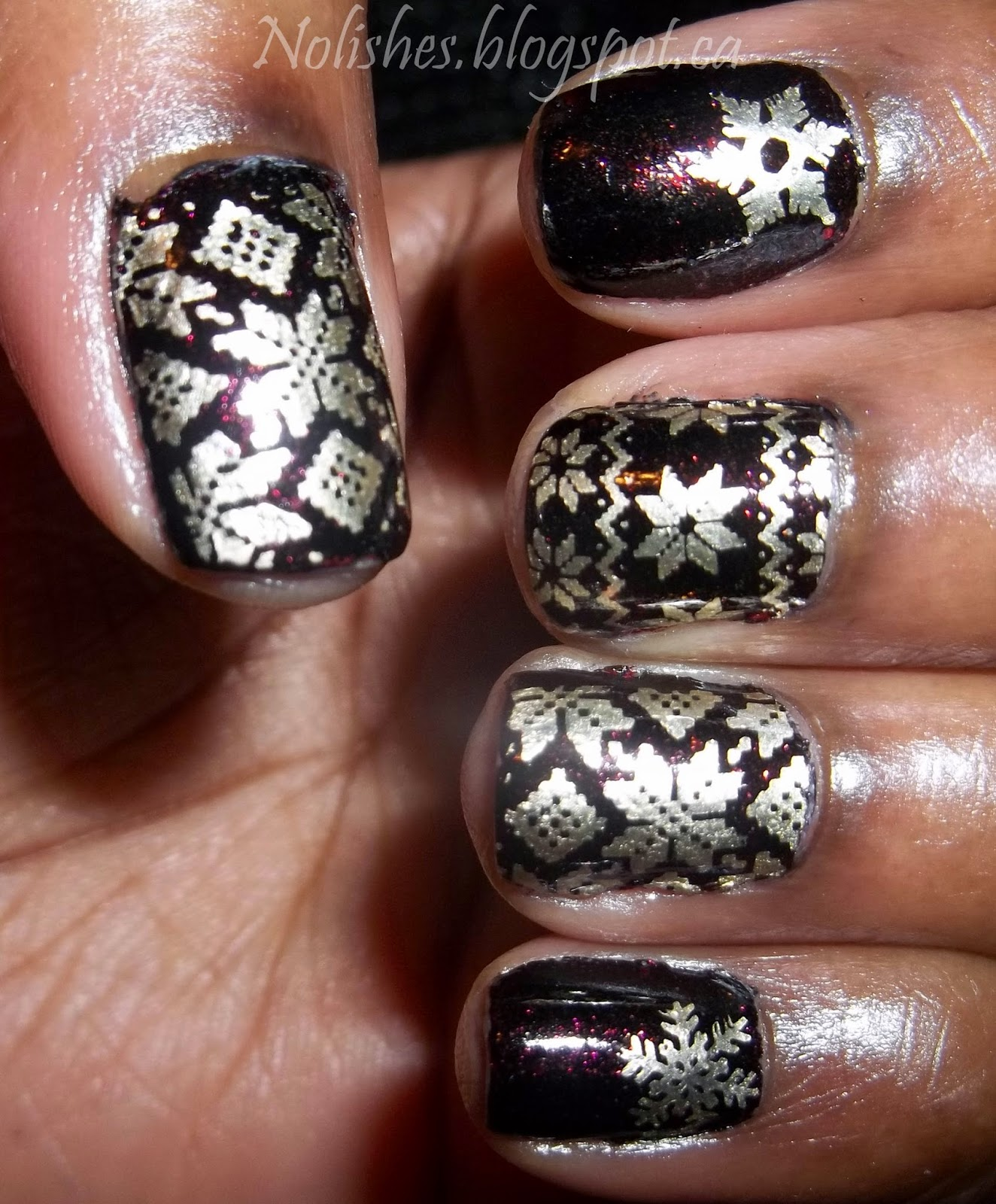 Nail stamping manicure featuring gold snowflake and nordic sweater prints, stamped over a black polish with deep red flecks of shimmer.