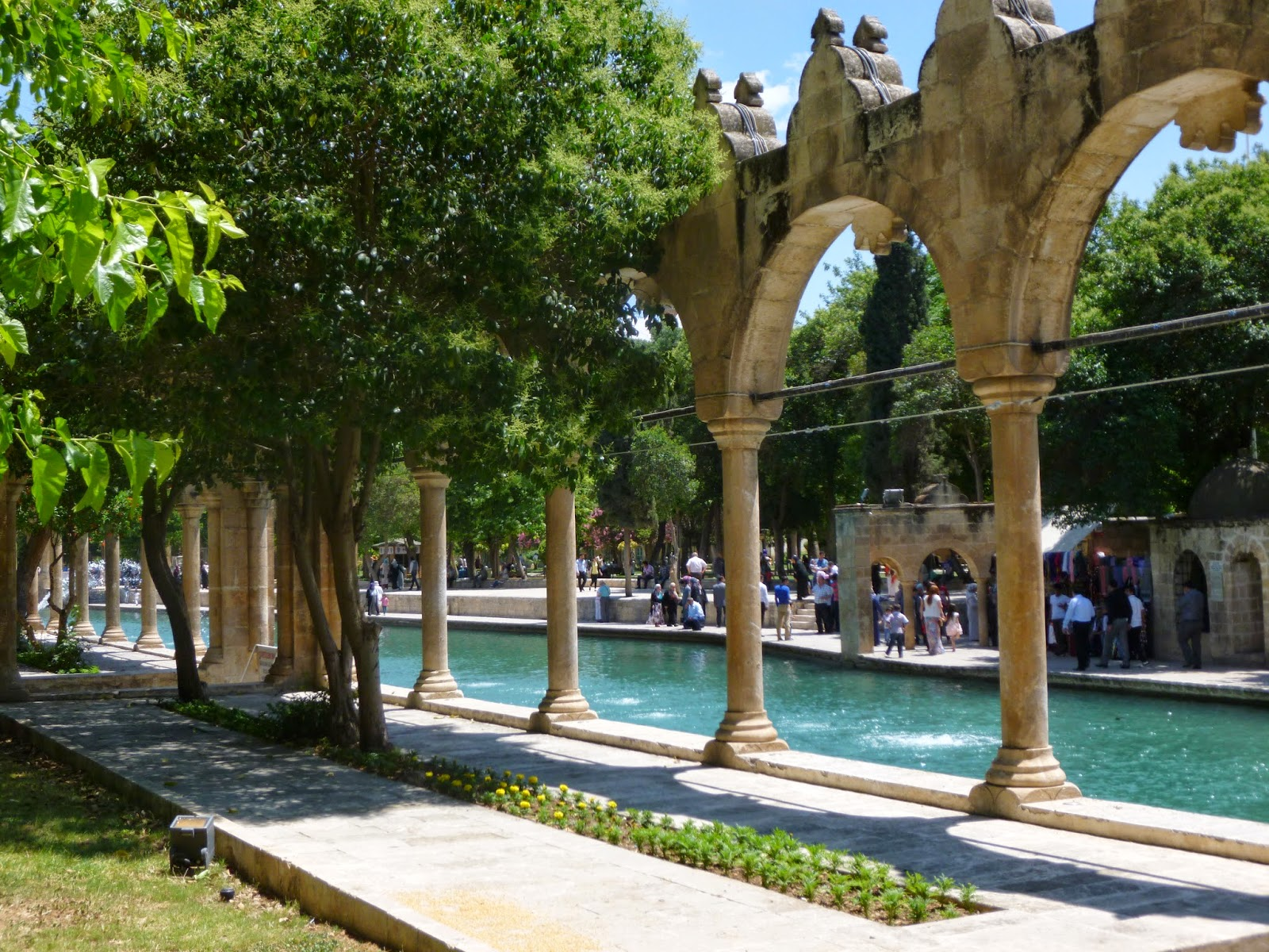 A brilliantly blue fish pool in Urfa, Turkey, bordered by white columns.