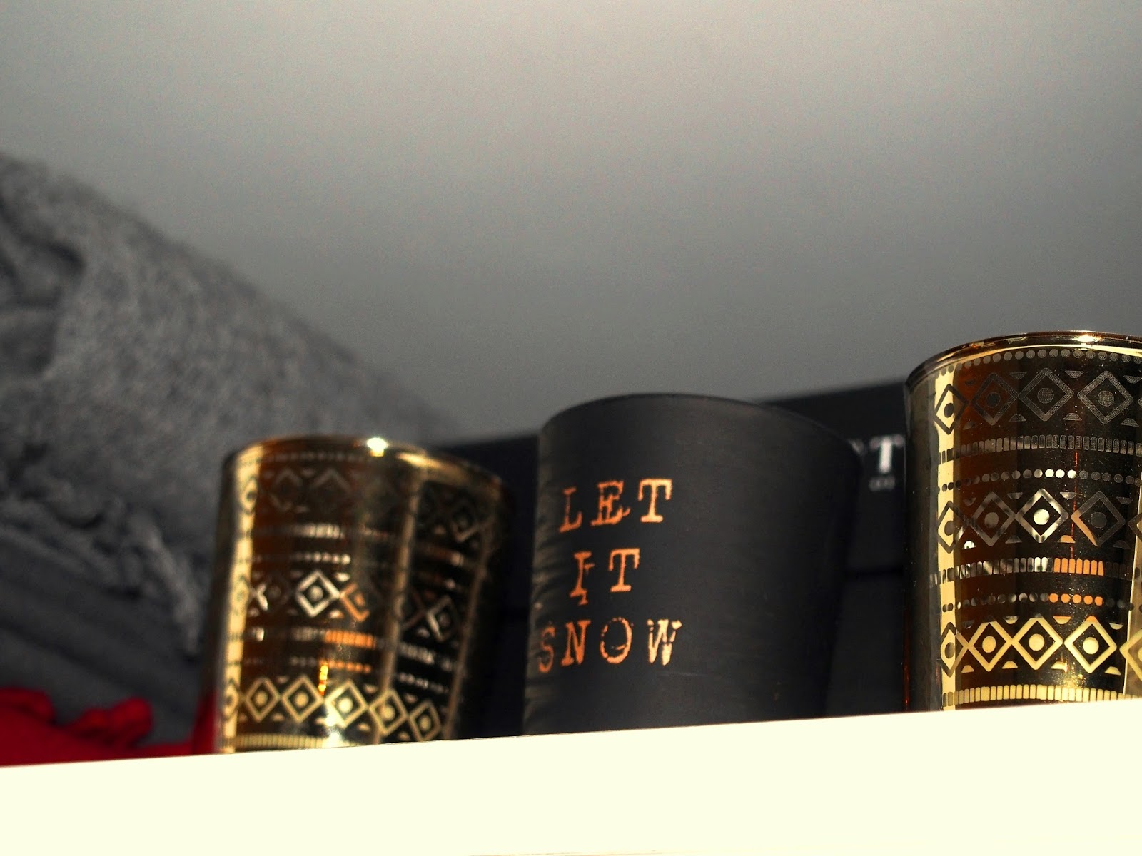 Jouluinen tunnelma eteisen kaapissa: kynttilöitä ja paksuja villaisia huiveja.