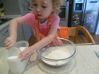 Measuring sugar into a bowl for muffin recipe