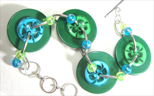 Bold fashion bracelet has Big green buttons, swirl flower buttons and shiny accent beads