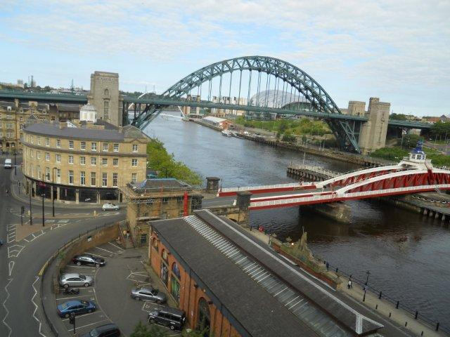 High-Level Bridge View, Newcastle-Upon-Tyne : Posted by Vibha Malhotra : After walking around the Castle Keep, I realized that I was just a few feet away from the High-Level Bridge. The bridge like any other bridge on Newcastle Quayside, connects Newcastle-Upon-Tyne to Gateshead. I couldn't resist and I decided to walk all the way to Gateshead.The entrance to the pedestrian walk on the High-Leve Bridge. Buses run in the middle. The bridge is fragile so traffic is restricted. The view on the left when walking from Newcastle to Gateshead. You can see the Millenium Bridge far in the distance and then the Magnificient Tyne Bridge and then nearest is the Swing bridge.A view of the buildings on the Newcastle Quayside. I love the colors of the buildings. They aren't candy colored as some of the buildings on the seaside but these colors suit the character of the city.The Castle Keep on the extreme left. All these shots have been taken from the High-Level Bridge. By now I am almost in the centre of the bridge. It was already 5:15 and I was running out of time for my adventures. So was now in a hurry to get to the other end. Some signs on one of the pillars of the bridge. The bridge was opened for use in 1850.Newcastle Skyline from the other end of the bridge.And now into Gateshead. The picture is just a proof of my expedition.Note the parking on the side of the streets. I think this practice makes the roads narrower than they already are. And now on the other side of the bridge. Headed back to Newcastle.View of the railway bridges on the other side of the bidge. Tyne is a huge river. Near my office it isn't as broad as it is near the bridges.The other side of the Newcastle Skyline. A lot of construction is in progress in the city. In fact, the University of Newcastle-Upon-Tyne is in middle of a makeover right now.It was a fine walk and required some daring since the bridge was more or less deserted. I am glad that I did this however. Every since I first saw the High-Level bridge, I had wanted to walk on it. So it is a mission accomplished.