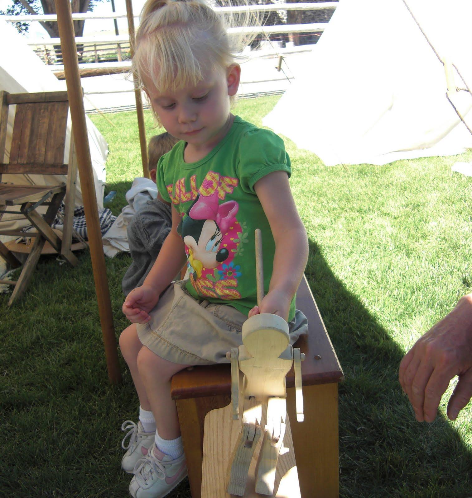 littlegirl tied up Little A had fun trying to make the wooden man jump.