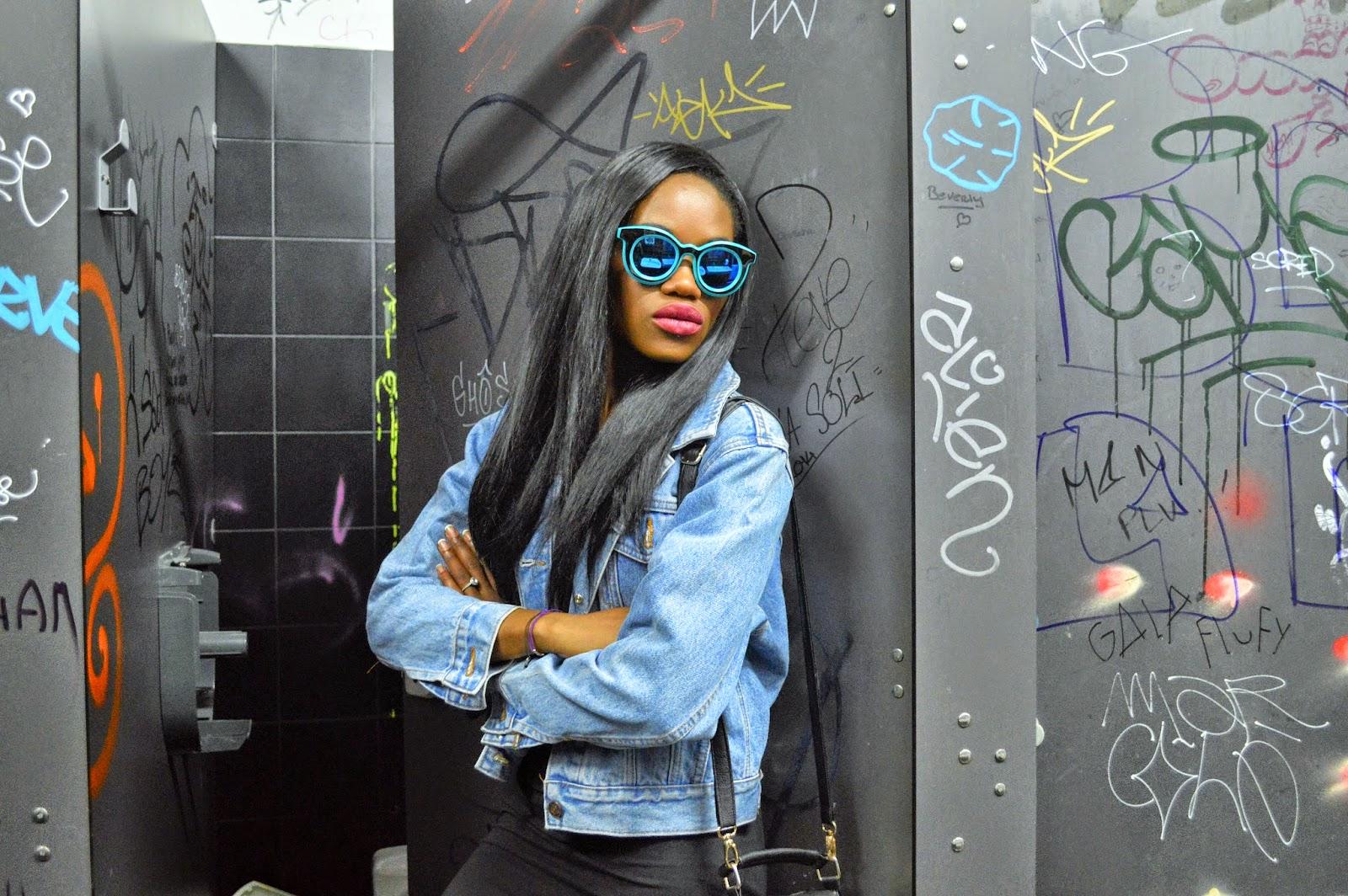 veste en jean, robe noire, sac à main, lunettes bleues