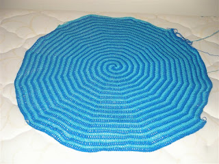 teal and royal blue spiral baby blanket covering almost the width of the mattress
