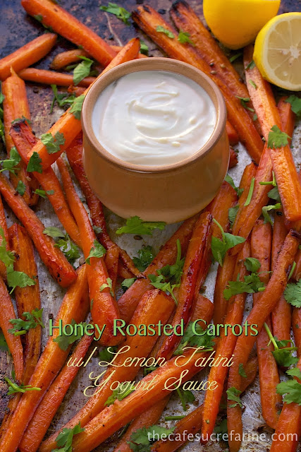 A vertical photo of a baking pan filled with Honey Roasted Carrots with a small jar of lemon tahini yogurt sauce in the middle and a graphic title at the bottom of the photo.