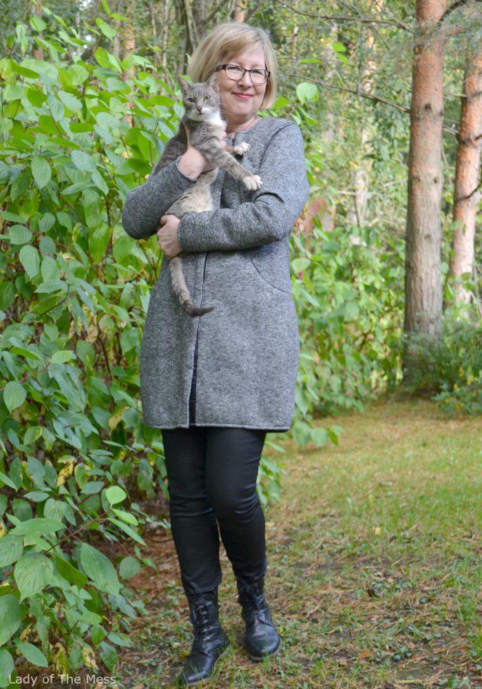 harmaa pitkä jakku ja mustat housut ja kissa