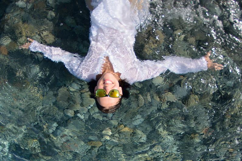 moteris su balta suknele gulinti ant vandens