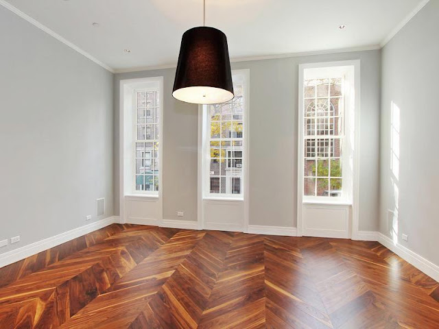 Living room with herringbone wood floor, black pendant light and tall encasement windows with white trim