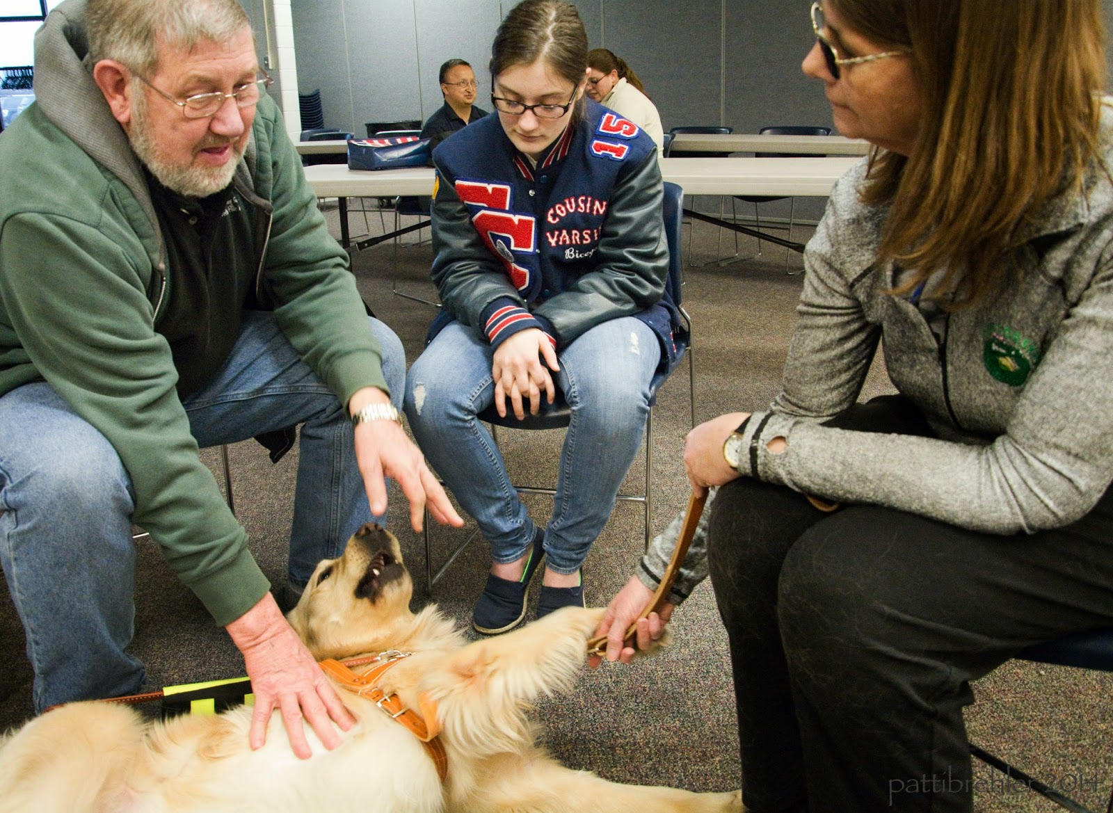 The man in the green sweatshirt is sitting on a chair on the left side, reaching to pet the golden retriever. The golden is lying on his side on the carpet, rolling over. Next to the man is a teenage girl with glasses and a varsity jacket and blue jeans. She is sitting in a chair looking down at the dog at her feet. On the right side is the woman with sunglasses wearing a grey shirt and black slacks. She is holding the dog's leash in her hands.