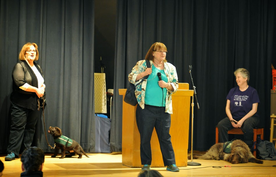 a volunteer holding the microphone on stage addresses the crowd of volunteers (guide dog puppies with their handlers are behind her).