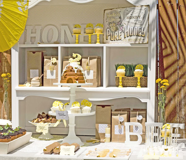 love this setup the bright yellow cupcake stands beehive cake and