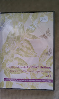 Photo of a DVD cover. It's a plastic case with a white cover with pale green leaves and butterflies stenciled on it. Near the bottom, in purple, it says, Highlights from the Conflict Hotline. What you say next can change your world. Volume 1. Featuring Miki Kashtan, co-found of Bay Area Nonviolent Communication.