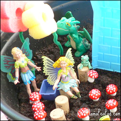 fairies, flowers, toadstools, frog, stepping stone corks and dragon in imaginary play garden