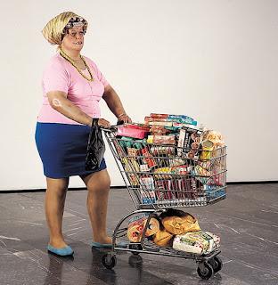 """Cette image est une photographie d'une des oeuvres de l'artiste américain Duane Hanson, sculpteur du courant de l'hyperréalisme. Son art représente une critique permanente de la société-type américaine. Il traite ses « sujets » avec tact, compassion et sympathie en mettant en évidence leur fragilité, leur résignation et, souvent, leur désespoir. L'oeuvre en question s'intitule """"Supermarket Lady"""", créée en 1969-1970 et exposée au Musée d'Art Contemporain Ludwig-Forum d'Aix-la-Chapelle. Sculpture en polyester et fibre de verre et réalisé à partir de modèle vivant, cette sculpture mêlant pop art et hyperréalisme fut terminée en 1969 mais présentée au public seulement en 1970. Les matériaux utilisés pour cette œuvre d'environ 166 cm sur 70 cm, sont très différents : métal,papier et plastique,fer, et de vrais vêtements, en plus de la structure de base énoncée plus haut. Contrairement à l'époque de Rodin (1840-1917) à qui l'on reprocha en 1877 d'avoir moulé L'Âge d'airain à partir d'un être vivant, ce qui visait à discréditer l'auteur en le traitant de falsificateur, les critères ont changé depuis les années 1960. C'est ainsi que relever les formes du mannequin fait partie de la conception de l'art de Duane Hanson. Comme Rodin, il cherche l'essentiel directement observable au quotidien et naturel.Cette œuvre est représentée en grandeur nature.Elle représente une femme américaine qui consomme beaucoup remplissant son caddie.  En Europe occidentale, il est assez improbable de croiser une ménagère portant des bigoudis et des chaussons et poussant un caddie, mais aux États-Unis, un tel personnage fait partie du quotidien, d'où son caractère « réaliste » dans ce contexte culturel et social. Cette œuvre traduit les symboles de la société de consommation en 1970. On note cette ménagère américaine issue de la petite Amérique qui a le regard vide, elle achète pour noyer le complexe de la pauvreté. Il ne faut pas oublier que la consommation est le marqueur de la réussite sociale. C"""