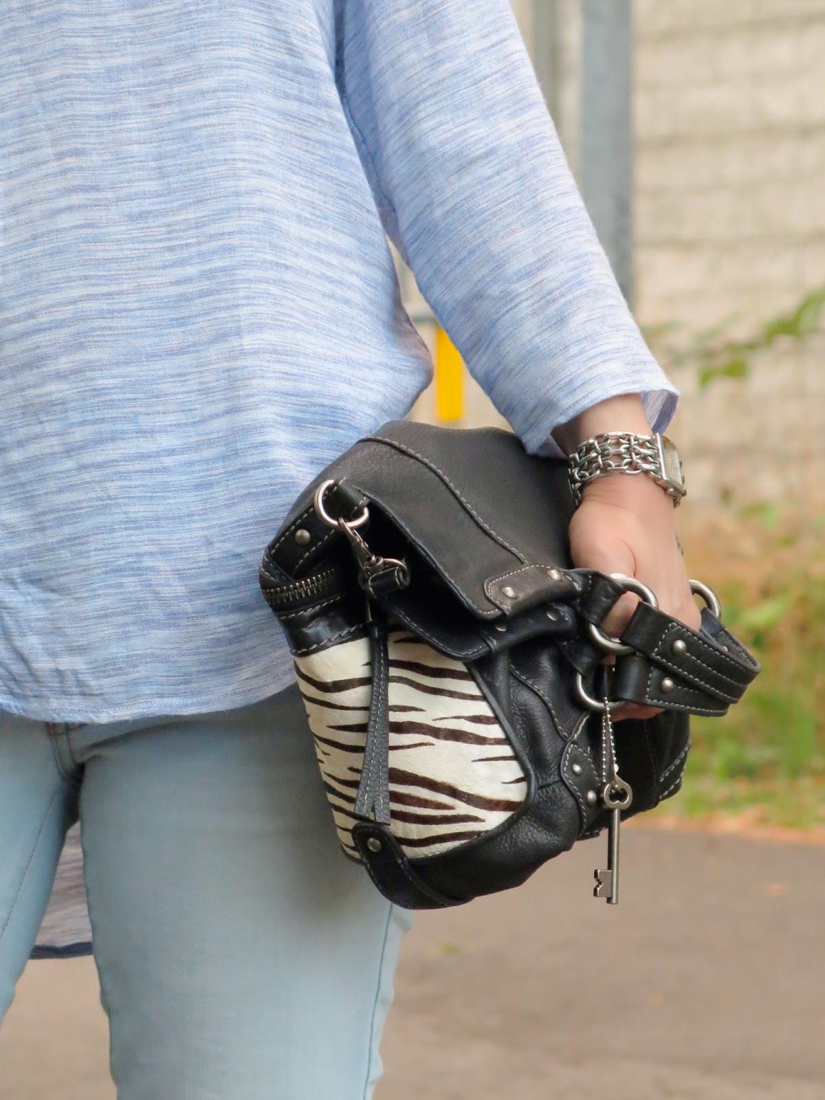 light-wash skinny jeans, snake-print pumps, and zebra-striped bag