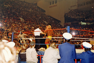 Hulk Hogan displays poor sportsmanship by attacking The Wizard with a Maple Leaf Gardens folding chair as Kim Chee cowers on the Toronto ringside ramp.