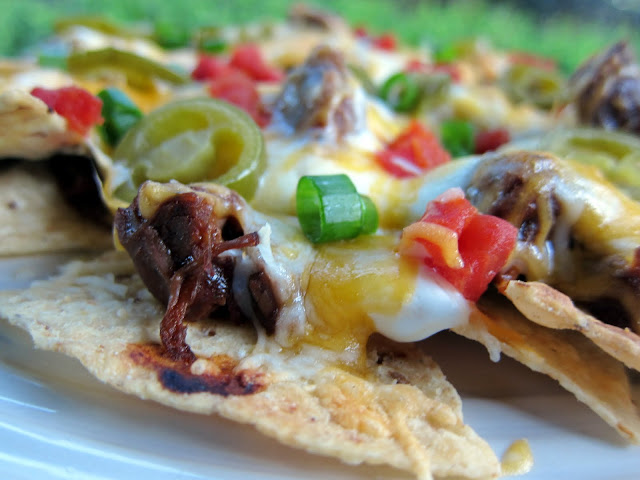 Pot Roast Nachos Recipe - use leftover pot roast to make amazing baked nachos! Pot roast, bbq sauce, chipotles, tortilla chips, cheese, sour cream, jalapeños, tomatoes and green onions. Copycat recipe from Ditka's in Chicago.