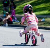 Kid riding a bike with training wheels