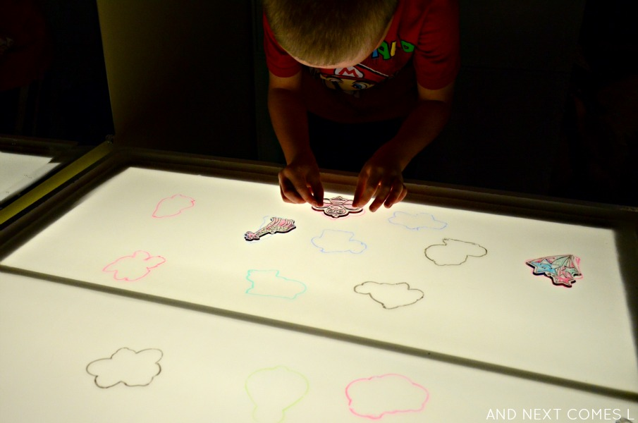 Creating a puzzle on the light table using dollar store sun catchers and dry erase markers from And Next Comes L