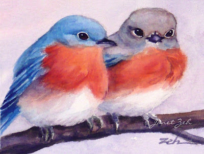 two bluebirds sit on a tree branch