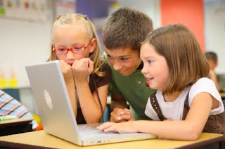 Three kids on playing on a laptop