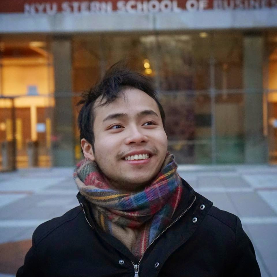 Ken Ruan wearing a winter jacket, a colorful scarf standing in from of the NYU Sterm School of Business.