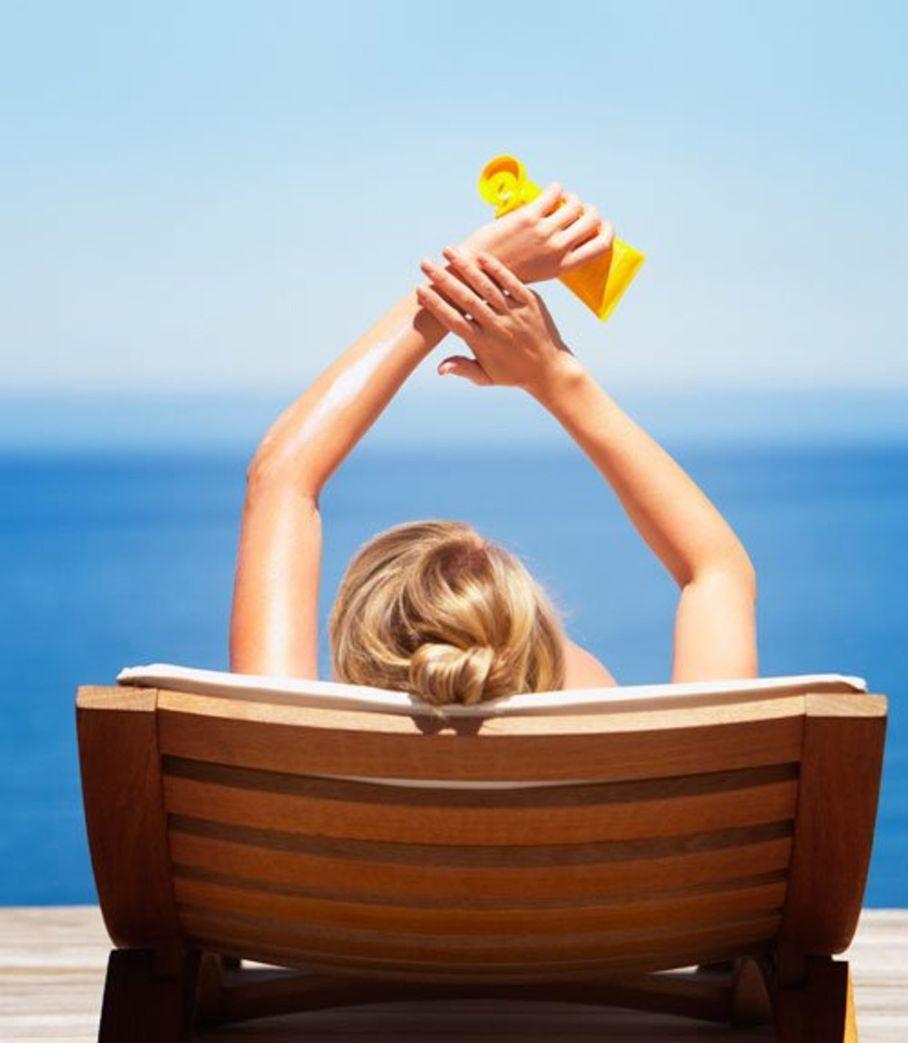 Girl putting on sunscreen