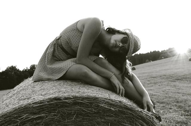 Mujer posando sobre una paja en el campo