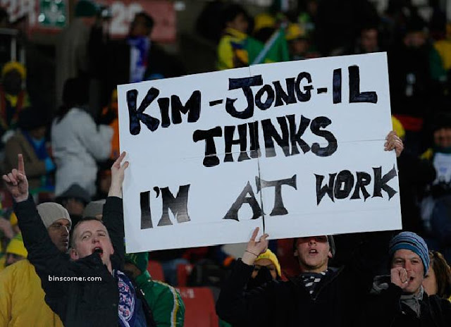 Fans hold up a sign reading Kim-Jong-Il thinks I'm at work