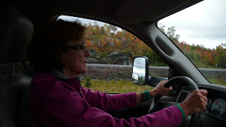Liz driving the truck with fall landscape outside.
