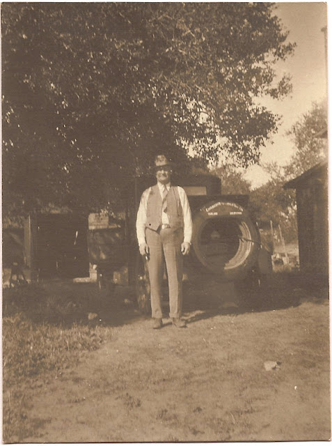 man in business suit circa 1920s standing near truck on dirt road or driveway