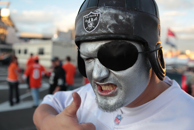 An Oakland Raiders fan wearing face paint, an eye patch and an old time football helmet.