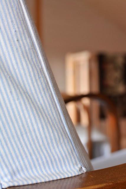 Muonamiehen mökki - Vanha nojatuoli ja ryijy porraskaiteella