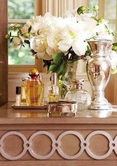 pretty white peonies in vase with perfumes