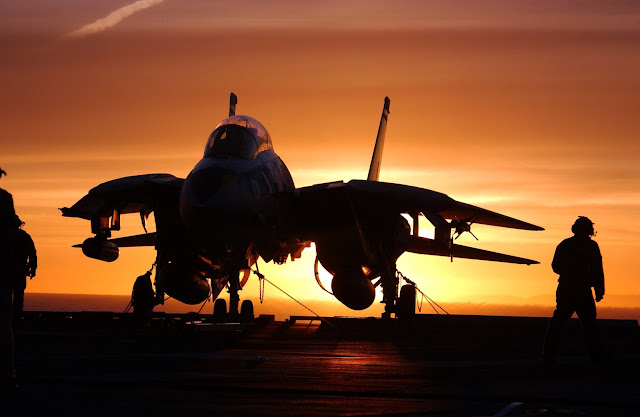 F-14D tied down on the deck with the sun setting.