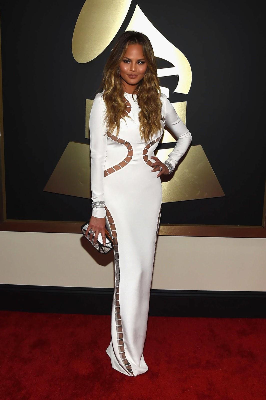 Chrissy Teigen wears a figure hugging white gown to the 2015 Grammy Awards in LA