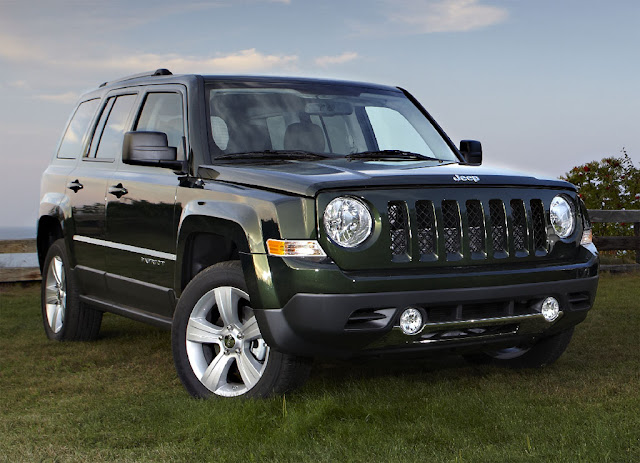 Front 3/4 view of black 2011 Jeep Patriot in rural setting