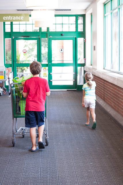 two kids pushing a cart out of the grocery store